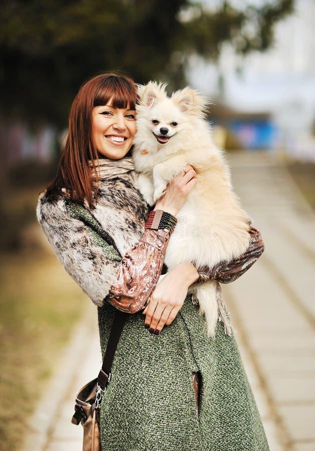 Jeune prise heureuse de femme dans les mains petit chien ou le chiot - por extérieur photos stock