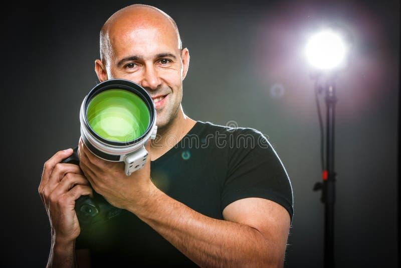 Jeune, pro photographe masculin dans son studio photo libre de droits