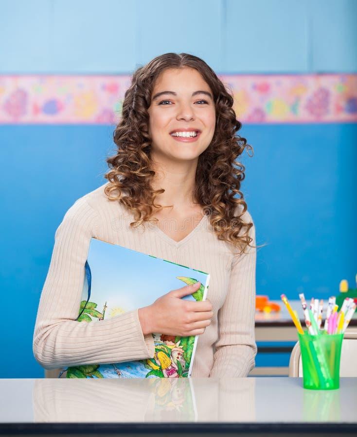 Jeune professeur With Book Sitting au bureau image libre de droits