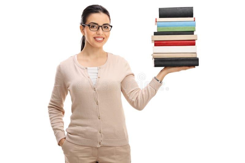 Jeune professeur féminin avec une pile de livres images stock