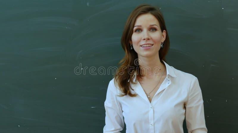 Jeune professeur féminin heureux parlant à la classe se tenant contre le conseil vert image libre de droits