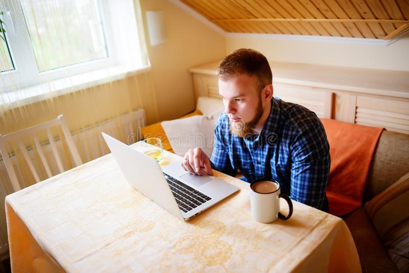 Jeune professionnel décontracté surfant l'Internet sur son ordinateur portable dans une salle à manger photos stock