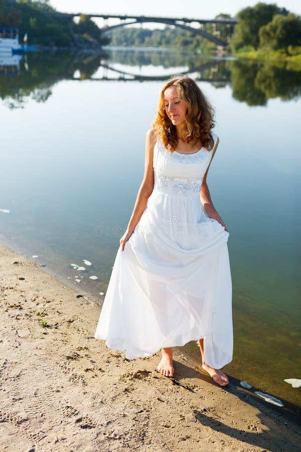 Jeune promenade gaie de jeune mariée de fille nu-pieds la côte ensoleillée de la rivière images libres de droits