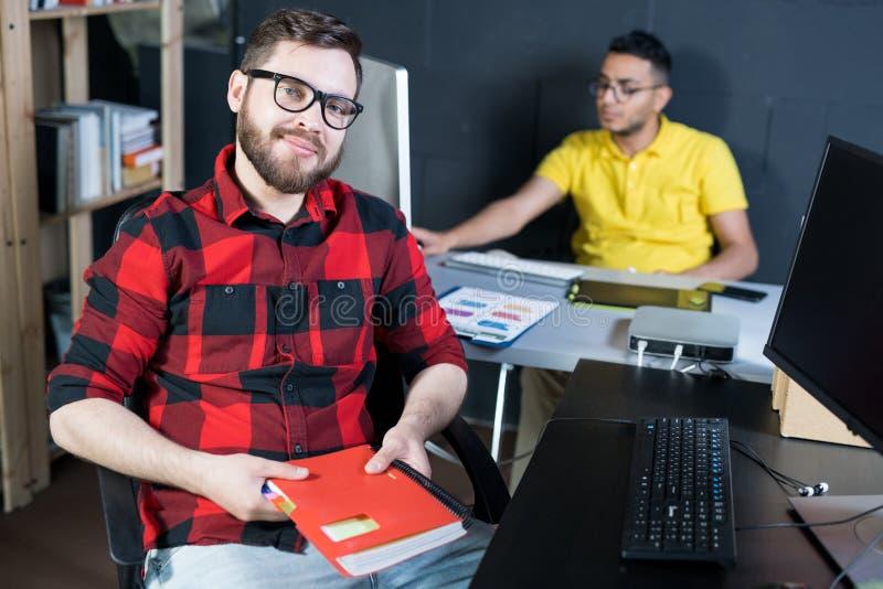 Jeune promoteur informatique créatif posant dans le bureau photos stock