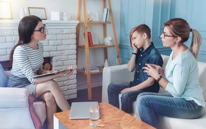 Jeune psychologue sérieux écoutant la mère de l'adolescent ennuyeux photo libre de droits