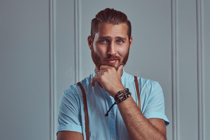 Jeune rétro homme roux élégant beau dans des bretelles posant contre un mur blanc dans un studio image stock