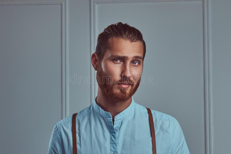 Jeune rétro homme roux élégant beau dans des bretelles posant contre un mur blanc dans un studio photographie stock libre de droits
