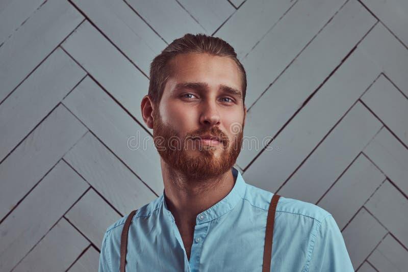 Jeune rétro homme roux élégant beau dans des bretelles posant contre un mur blanc dans un studio photo stock