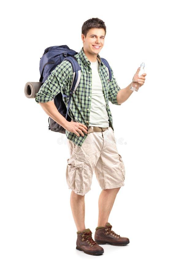 Jeune randonneur retenant une bouteille de l'eau image libre de droits