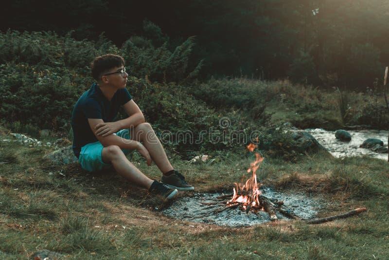 Jeune randonneur s'asseyant à côté de la cheminée et le feu et la pensée photos libres de droits