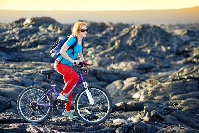 Jeune recyclage de touristes sur le gisement de lave sur Hawaï Randonneur féminin se dirigeant au secteur de visionnement de lave images libres de droits