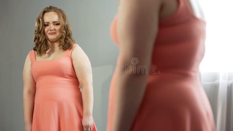 Jeune regard femelle dans le miroir avec dégoût, honteux du gros corps, question d'obésité photo stock