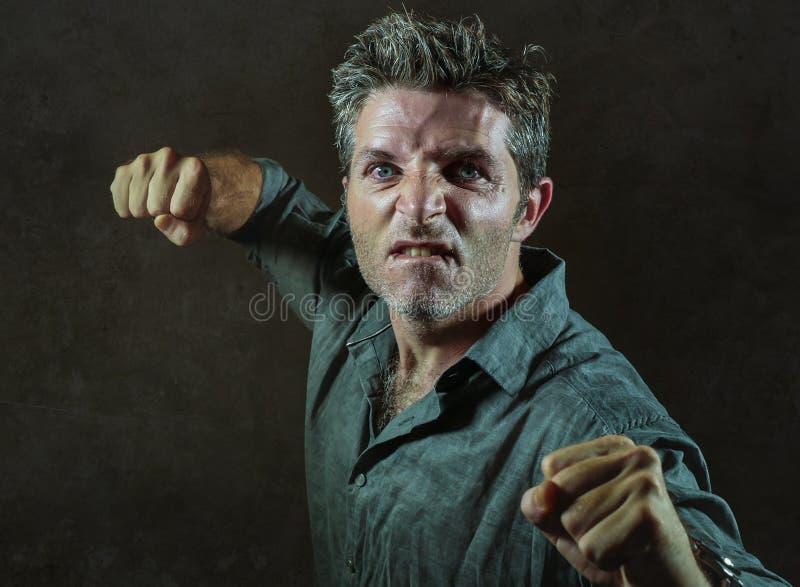 Jeune renversement et homme agressif dans le bar soulevant le poinçon de lancement menaçant de poing prêt à combattre comme faute photo stock