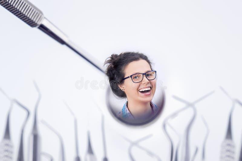 Jeune rire femelle gai dans le miroir d'un dentiste photos stock