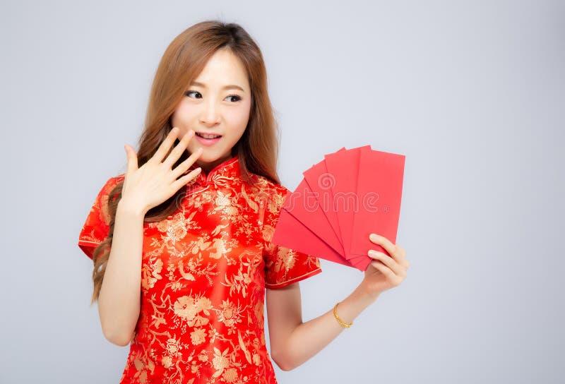 Jeune robe asiatique de cheongsam de femme de beau portrait souriant tenant l'enveloppe rouge sur le fond blanc photo stock