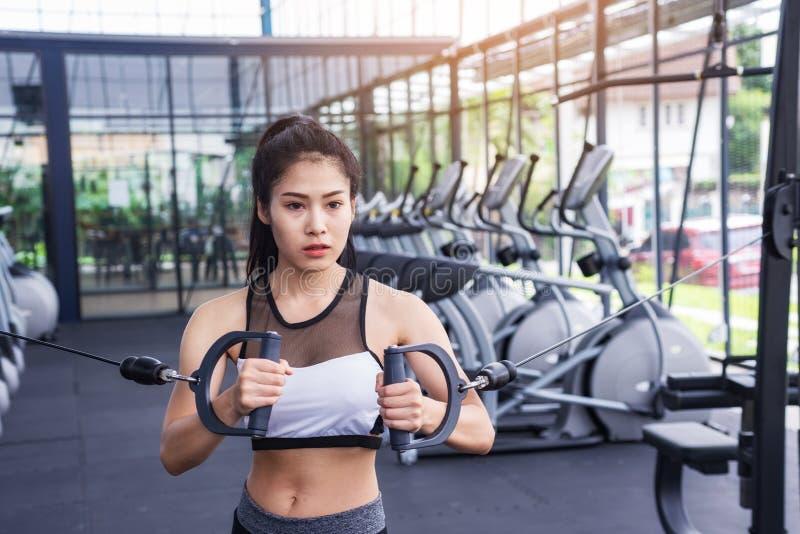 Jeune séance d'entraînement d'exercice de femme de forme physique avec le câble d'exercice-machine dans le gymnase de centre de f images stock