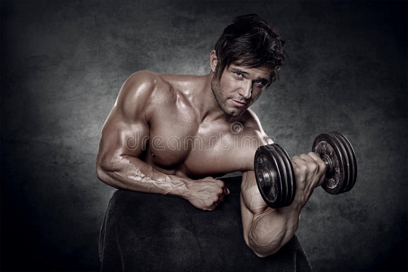 Jeune séance d'entraînement sexy musculaire d'homme dans le gymnase photos stock