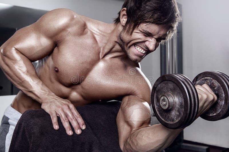Jeune séance d'entraînement sexy musculaire d'homme dans le gymnase photo stock