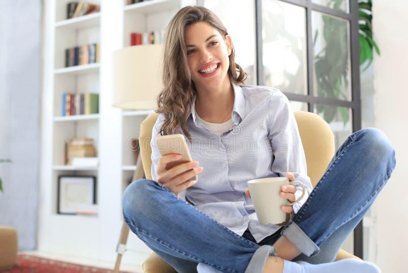 Jeune séance femelle de sourire dans le fauteuil dans le salon et utilisation avec son téléphone portable images stock