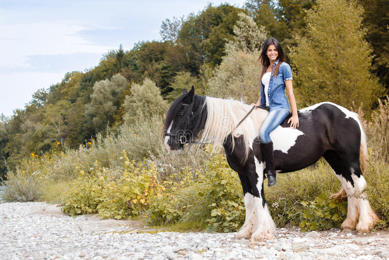 Jeune séance femelle sur son cheval et regarder c image stock