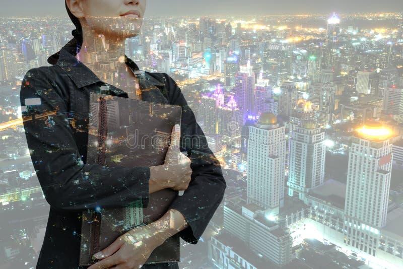 Jeune sac de participation de femme d'affaires de double exposition avec le paysage de la ville la nuit photographie stock