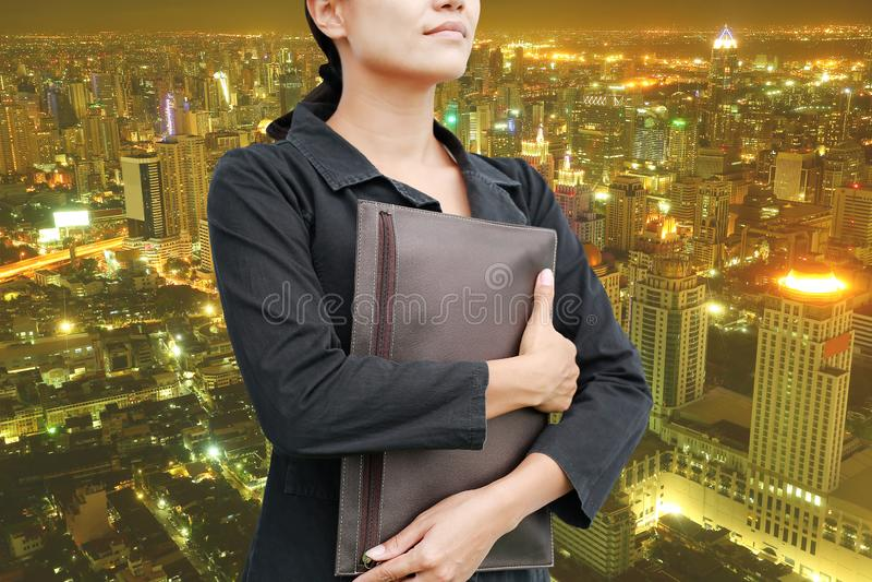 Jeune sac de participation de femme d'affaires de double exposition avec le paysage de la ville la nuit image libre de droits