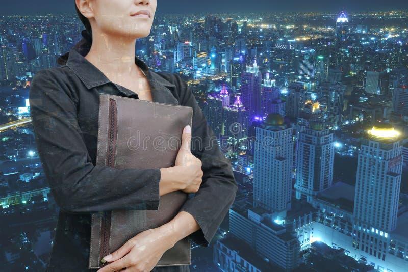 Jeune sac de participation de femme d'affaires de double exposition avec le paysage de la ville la nuit image stock