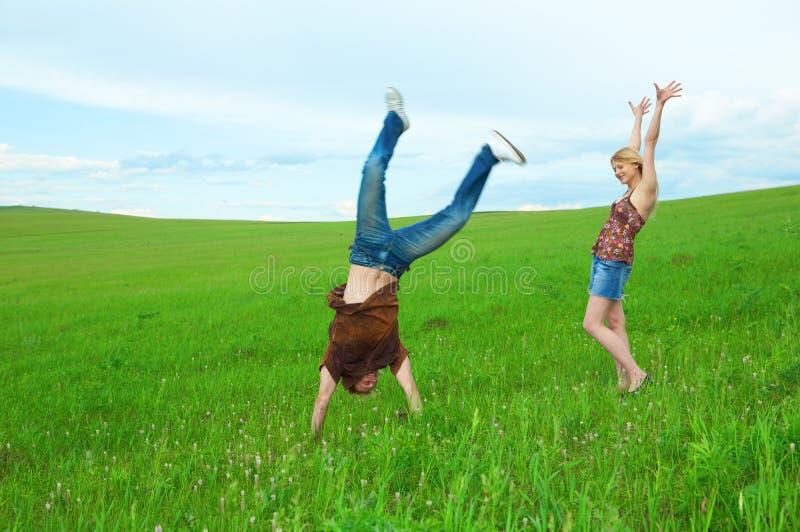 Jeune saut de couples autour dans la nature photo stock