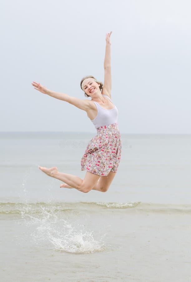 Jeune sauter heureux de femme photo stock
