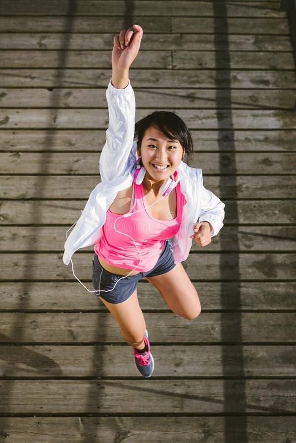 Jeune sauter heureux sportif de femme photo stock