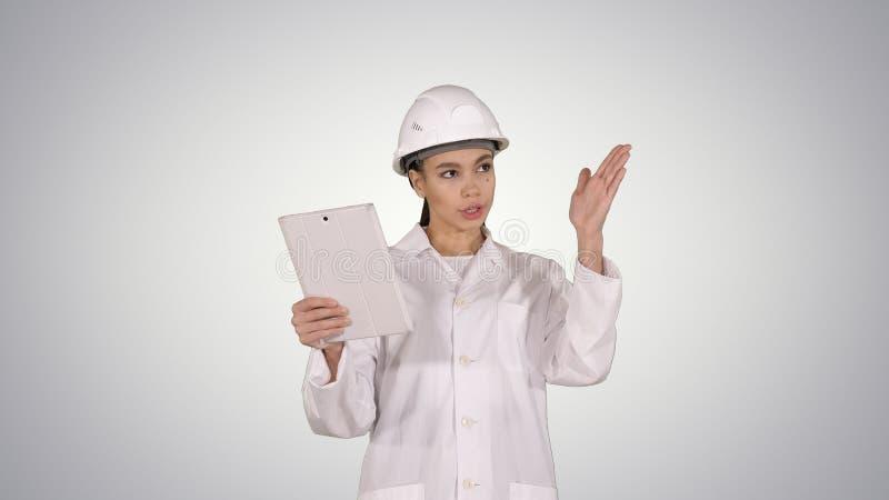 Jeune scientifique féminin Making Video Call avec la Tablette sur le fond de gradient images stock