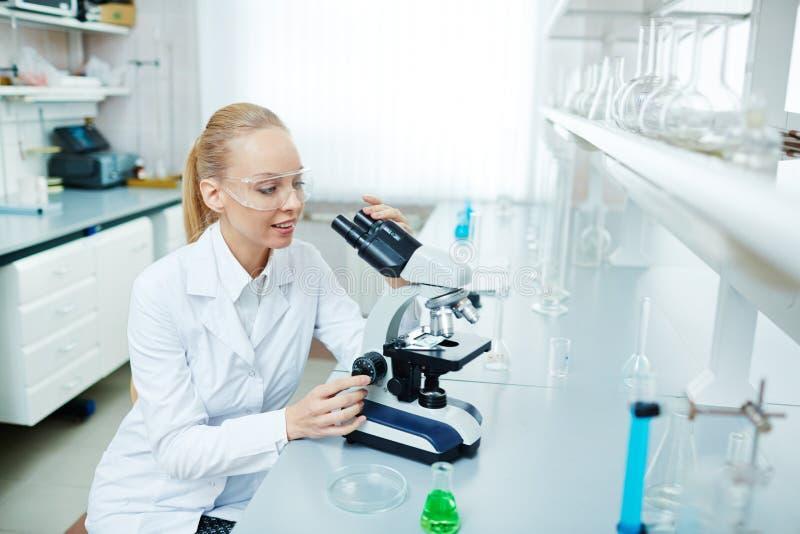 Jeune scientifique féminin travaillant avec le microscope dans le laboratoire photo stock