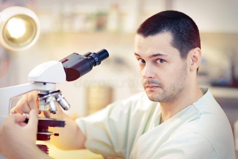 Jeune scientifique masculin drôle avec le microscope image stock