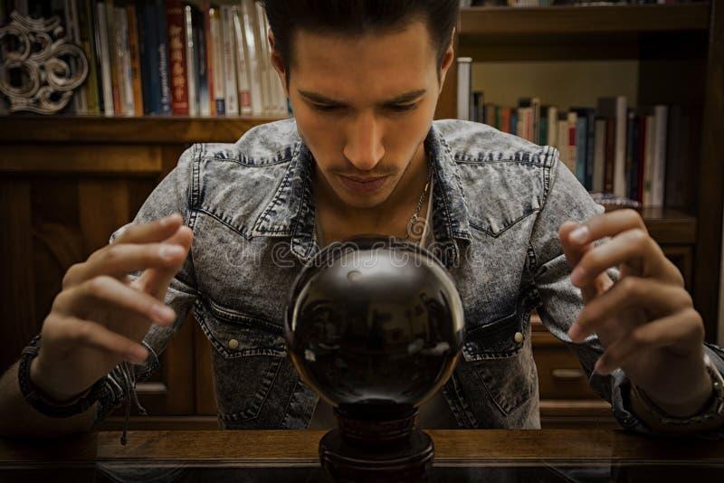 Jeune scombre masculin prédisant l'avenir par le regard dans la boule de cristal photos stock