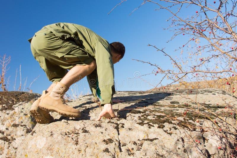 Jeune scout masculin Climbing une roche au champ photographie stock