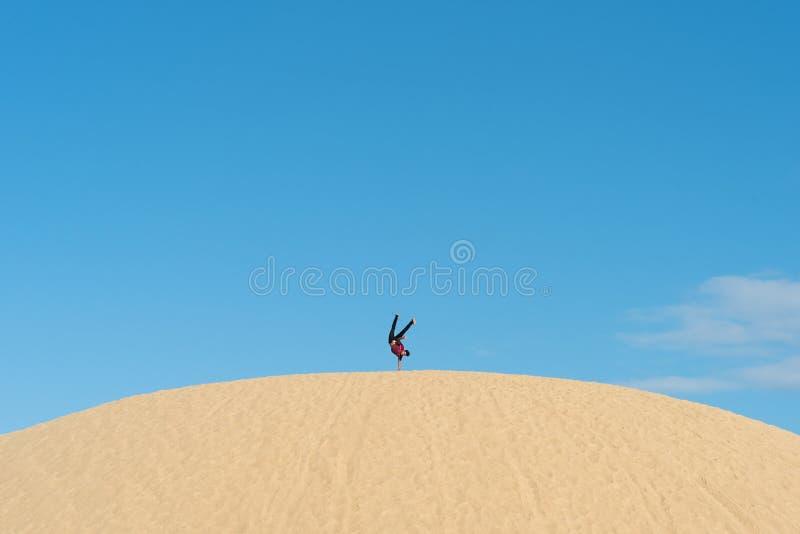 Jeune secousse masculine asiatique à l'envers sur une dune de sable images stock