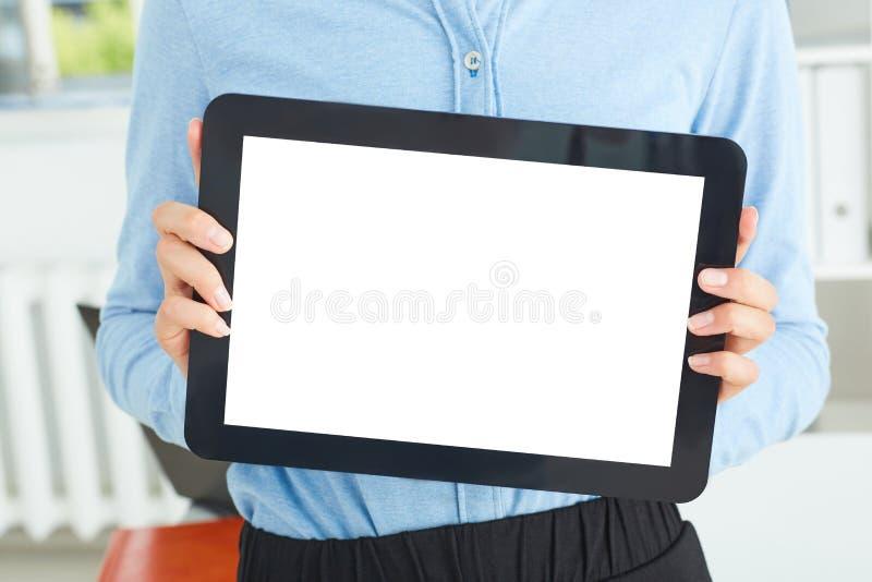 Jeune secrétaire de famale tenant le comprimé dans des mains se reposant au bureau photo libre de droits