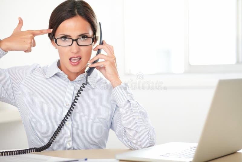 Jeune secrétaire féminin à l'aide du téléphone images stock