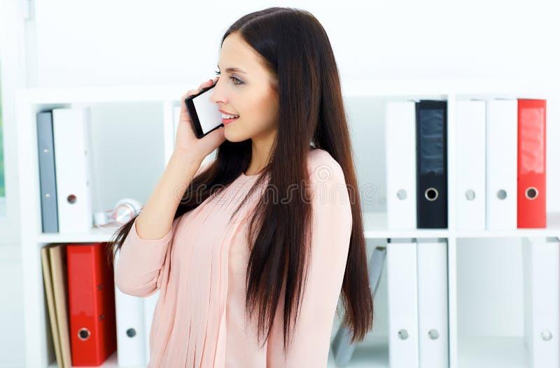 Jeune secrétaire féminin de sourire de brune parlant au téléphone photographie stock libre de droits
