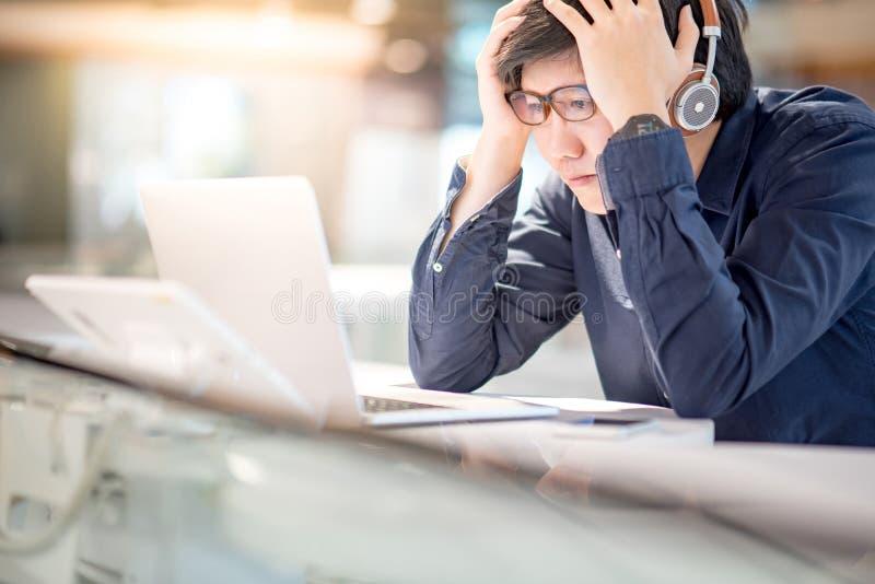 Jeune sentiment asiatique d'homme d'affaires soumis à une contrainte tout en travaillant avec le recouvrement image libre de droits