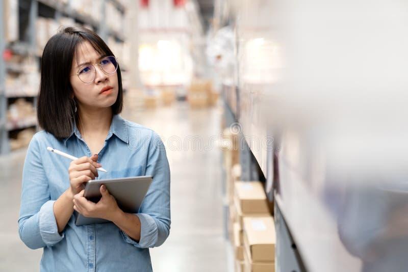 Jeune sentiment asiatique malheureux franc de femme, de commissaire aux comptes ou d'employés confus dans le magasin d'entrepôt V photographie stock libre de droits