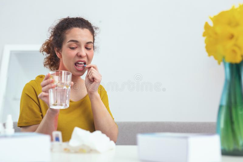 Jeune sentiment patient prudent tout en prenant des pilules photo stock