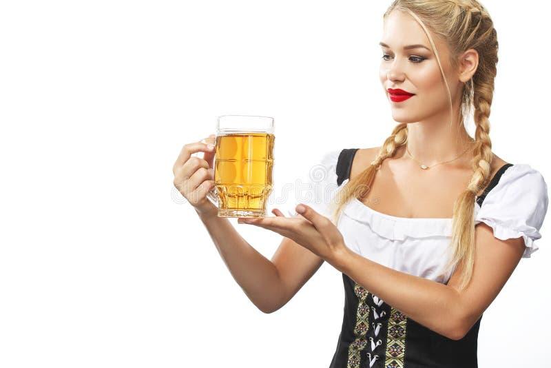 Jeune serveuse sexy d'Oktoberfest, portant une robe bavaroise traditionnelle, tasse de bière servante sur le fond blanc photo libre de droits