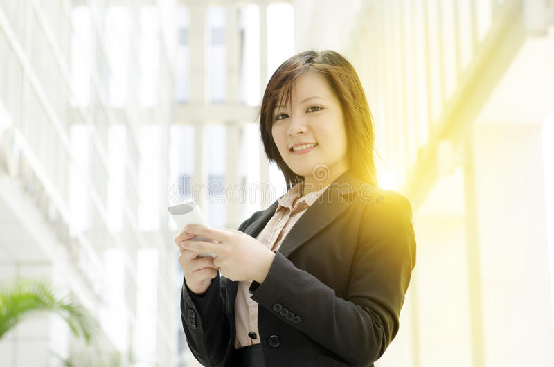 Jeune service de mini-messages asiatique de femme d'affaires sur le smartphone photos libres de droits