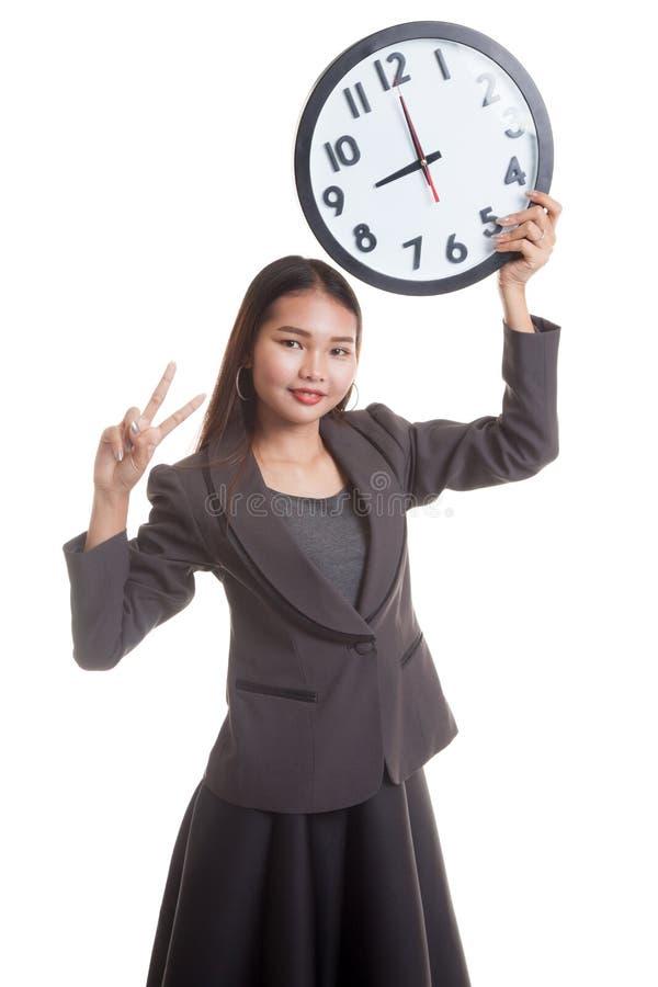 jeune signe asiatique de victoire d 39 exposition de femme d 39 affaires avec une horloge photo stock. Black Bedroom Furniture Sets. Home Design Ideas