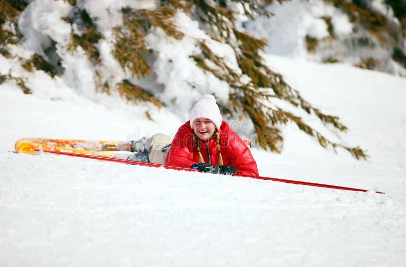 Jeune skieur féminin mignon après être tombé vers le bas images stock