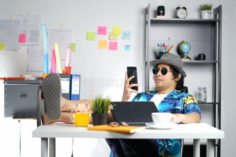 Jeune Smartphone de vérification professionnel élégant, jambes sur le Tableau Wh photo stock