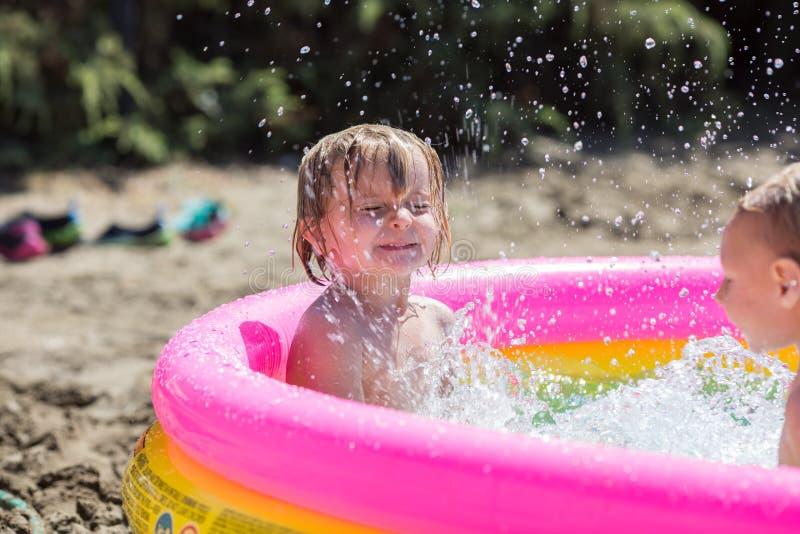 Jeune soeur blonde de fille d'enfant et son frère jouant dans la petite piscine avec de l'eau Lumière chaude de coucher du soleil image libre de droits