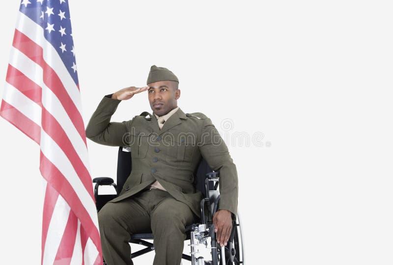 Jeune soldat des USA dans le fauteuil roulant saluant le drapeau américain au-dessus du fond gris photographie stock libre de droits