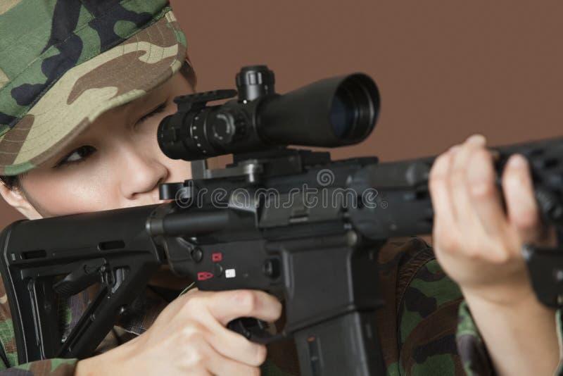 Jeune soldat des USA Marine Corps de femelle visant le fusil d'assaut M4 au-dessus du fond brun photographie stock libre de droits